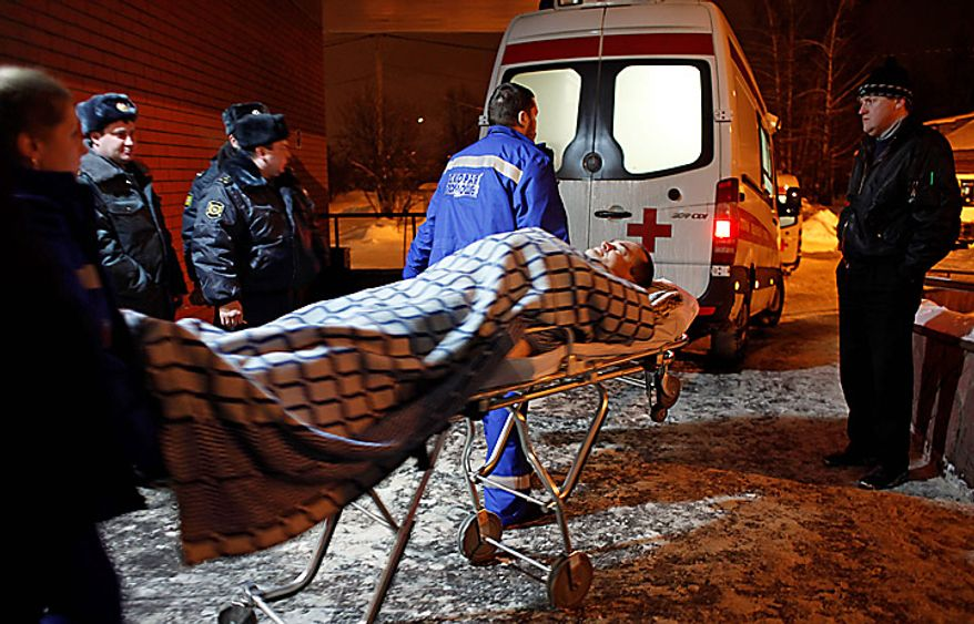 A wounded blast victim  is wheeled in a hospital near Domodedovo Airport in Moscow, Monday, Jan. 24, 2011. A suicide bomber set off an explosion that ripped through Moscow's busiest airport on Monday, coating its international arrivals terminal in blood. The attack killed  dozens of people and wounded more than a hundred.  (AP Photo/Alexander Zemlianichenko)