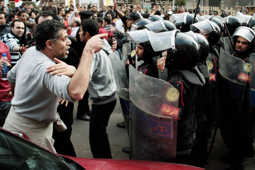 A demonstrator confronts riot police in Cairo on Tuesday during a Tunisia-inspired demonstration to demand the end of President Hosni Mubarak's nearly 30 years in power. Demonstrators called for and end to poverty, corruption and police abuses. (Associated Press)