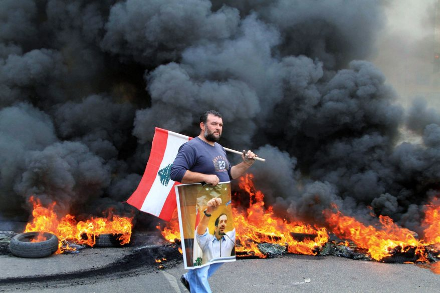 INFLAMED EMOTIONS:  A man walks in front of burning tires Tuesday in Sidon, Lebanon. Sunnis protested the rising power of the Shiite militant group Hezbollah. (Associated Press)