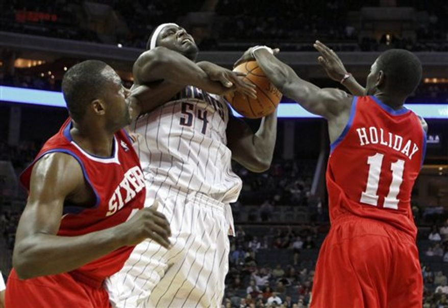 Charlotte Bobcats' Kwame Brown, center, battles for control of a rebound with Philadelphia 76ers' Jrue Holiday, right, and Elton Brand, left, in the second half of the Bobcats' 100-97 win in an NBA basketball game in Charlotte, N.C., Thursday, Jan. 20, 2011. (AP Photo/Chuck Burton)