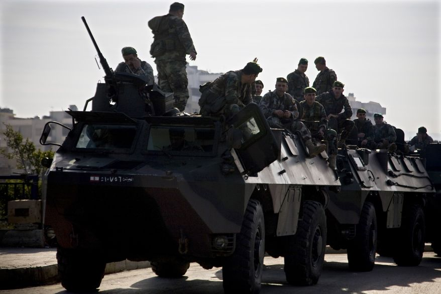 """Lebanese soldiers atop their armored vehicles secure the area in Beirut Tuesday, Jan. 25, 2011. Security forces are fanning out across Lebanon after Sunni lawmakers called for a nationwide """"day of rage"""" Tuesday to protest Hezbollah's gains in the government. (AP Photo/Grace Kassab)"""