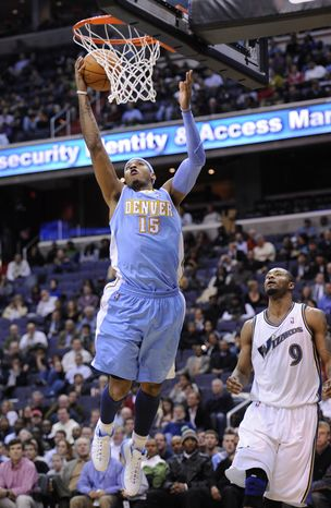 Denver Nuggets forward Carmelo Anthony (15) goes to the basket against Washington Wizards forward Rashard Lewis (9) during the first half of an NBA basketball game, Tuesday, Jan. 25, 2011, in Washington. (AP Photo/Nick Wass)