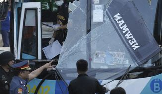 Philippine National Police investigators gathers evidence on a damaged passenger bus following an explosion at the financial district of Makati, Philippines on Tuesday Jan. 25, 2011. The powerful explosion ripped through the air-conditioned bus Tuesday killing several people and wounding more than a dozen others. (AP Photo/Aaron Favila)