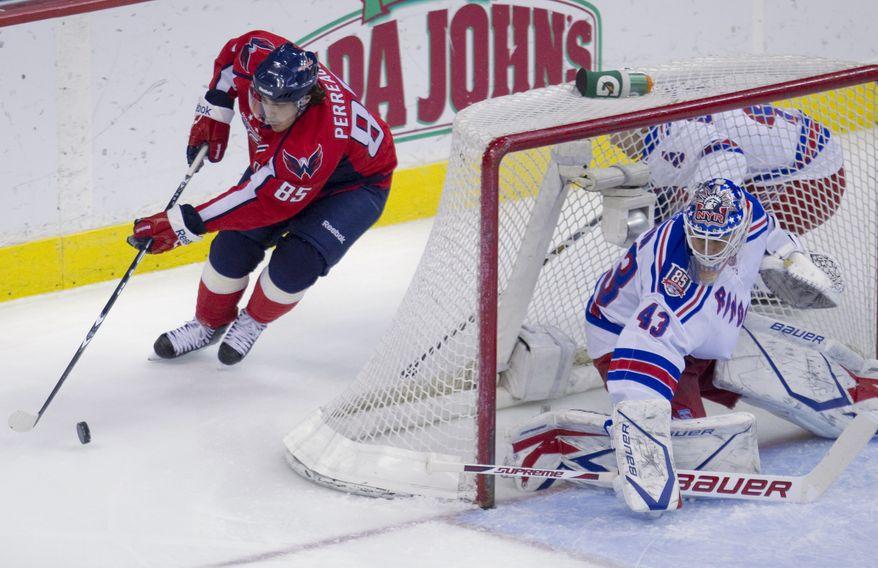 Washington Capitals center Mathieu Perreault (85) skates towards New York Rangers goalie Martin Biron (43) during the first period of an NHL hockey game on Monday, Jan. 24, 2011, in Washington. (AP Photo/Evan Vucci)