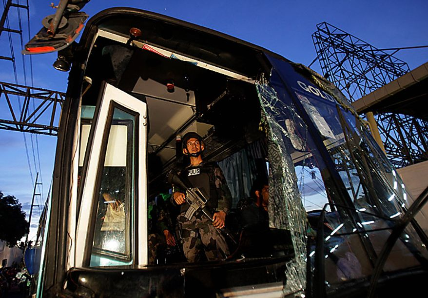 A Philippine National Police SWAT member stands guard inside a damaged passenger bus following an explosion at the financial district of Makati, Philippines, Tuesday Jan. 25, 2011. The powerful explosion ripped through the air-conditioned bus Tuesday killing several people and wounding more than a dozen others. (AP Photo/Aaron Favila)