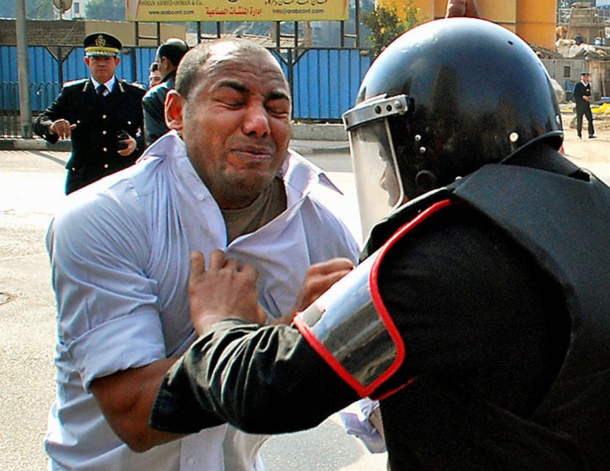 A protester scuffles with a riot policeman as he demonstrates in downtown Cairo, Egypt, Tuesday, Jan. 25, 2011. Hundreds of anti-government protesters marched in the Egyptian capital chanting against President Hosni Mubarak and calling for an end to poverty. (AP Photo/Mohammed Abu Zaid)