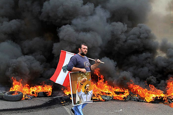 A protester carries a picture of outgoing Prime Minister Saad Hariri and a Lebanese flag as he walks in front of burning tires in the southern port city of Sidon, Lebanon, Tuesday, Jan. 25, 2011. Sunnis protested the rising power of the Shi'ite militant group Hezbollah on Tuesday, burning tires and torching a van belonging to Al Jazeera as Lebanese lawmakers gave the militant group's pick for prime minister enough support to form the next government. (AP Photo/Mohammed Zaatari)