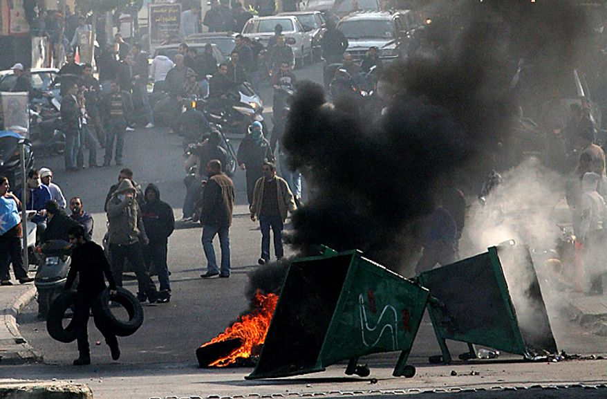Sunni protesters burn tires to block roads in Beirut, Lebanon, Tuesday, Jan. 25, 2011. Sunnis protested the rising power of the Shi'ite militant group Hezbollah on Tuesday, burning tires and torching a van belonging to Al Jazeera as Lebanese lawmakers gave the militant group's pick for prime minister enough support to form the next government. (AP Photo)