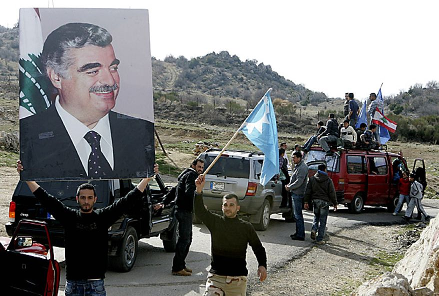 """Sunni men carry a picture of slain former Prime Minister Rafik Hariri, during a protest in the southern village of Chebaa on Lebanon's border with Syria's Israeli-occupied Golan Heights, Lebanon, Tuesday, Jan. 25, 2011. Thousands of Sunnis waved flags and burned tires Tuesday in a """"day of rage"""" to protest gains by the Shi'ite militant group Hezbollah, which is on the brink of controlling Lebanon's next government. (AP Photo/Lutfallah Daher)"""