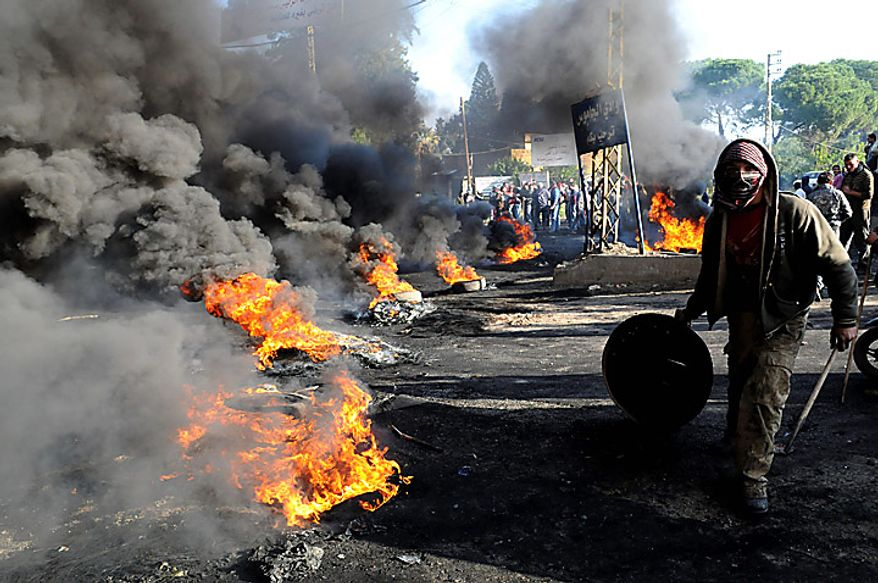"A Sunni protester burns tires in the northern Akkar region, Lebanon, Tuesday, Jan. 25, 2011. Thousands of Sunnis waved flags, burned tires and torched a van belonging to Al Jazeera on Tuesday during a ""day of rage"" to protest gains by the Shi'ite militant group Hezbollah, which now has enough support in parliament to control Lebanon's next government. (AP Photo/Ahmad Omar)"