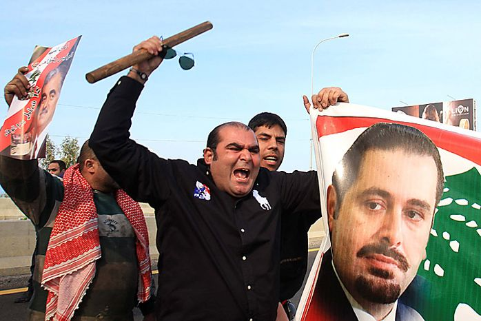 """Sunni protesters carry a picture of Lebanese caretaker Prime Minister Saad Hariri as they shout slogans in Jiyeh, south of Beirut, Lebanon, Tuesday, Jan. 25, 2011.Thousands of Sunnis waved flags and burned tires Tuesday in a """"day of rage"""" to protest gains by the Shi'ite militant group Hezbollah, which is on the brink of controlling Lebanon's next government. (AP Photo/Mohammed Zaatari)"""