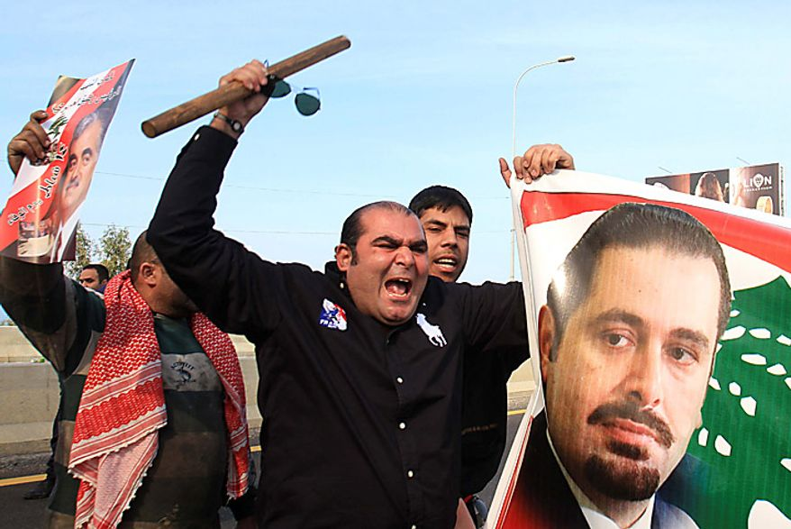 "Sunni protesters carry a picture of Lebanese caretaker Prime Minister Saad Hariri as they shout slogans in Jiyeh, south of Beirut, Lebanon, Tuesday, Jan. 25, 2011.Thousands of Sunnis waved flags and burned tires Tuesday in a ""day of rage"" to protest gains by the Shi'ite militant group Hezbollah, which is on the brink of controlling Lebanon's next government. (AP Photo/Mohammed Zaatari)"