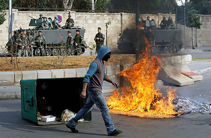 """A masked Sunni protester walks in front of burning garbage containers in Beirut, Lebanon, Tuesday, Jan. 25, 2011. Thousands of Sunnis waved flags and burned tires Tuesday in a """"day of rage"""" to protest gains by the Shi'ite militant group Hezbollah, which is on the brink of controlling Lebanon's next government. (AP Photo/Bilal Hussein)"""