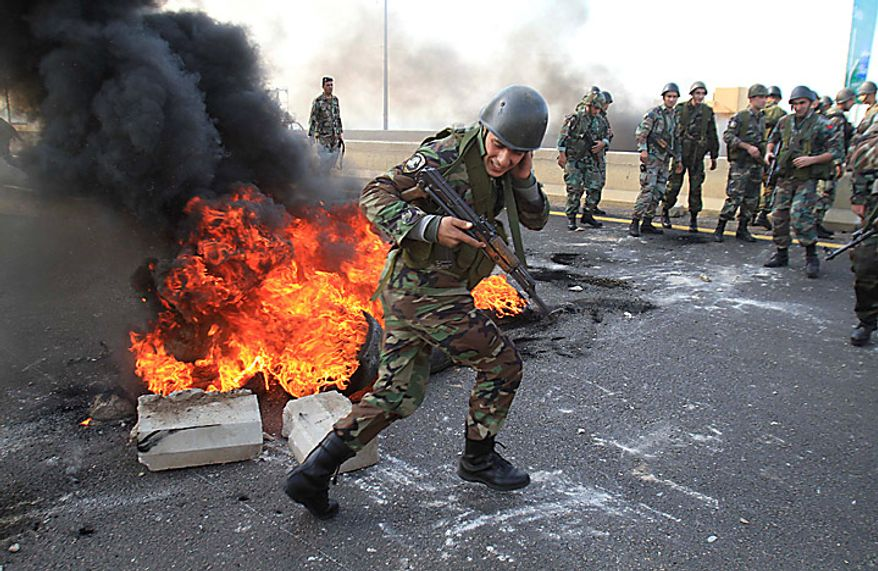 "A Lebanese soldier reacts after protesters burned tires on the highway in Jiyeh, south of Beirut, Lebanon, Tuesday, Jan. 25, 2011. Thousands of Sunnis waved flags and burned tires Tuesday in a ""day of rage"" to protest gains by the Shi'ite militant group Hezbollah, which is on the brink of controlling Lebanon's next government. (AP Photo/Mohammed Zaatari)"