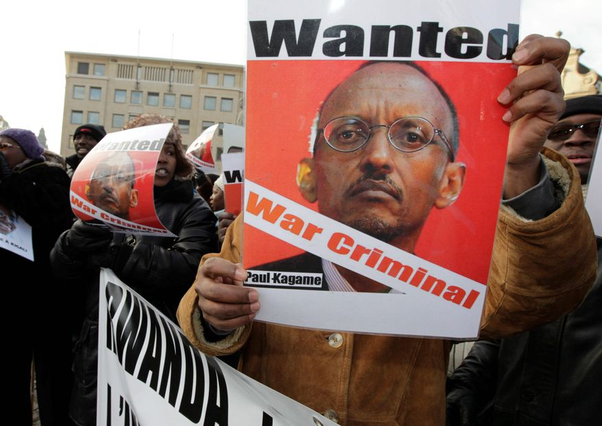 A man shows a poster of Rwandan President Paul Kagame to protest against his visit in Brussels last month. Four men who were once members of Mr. Kagame's inner circle have now fled the country. They say they fear for their lives even in exile as Mr. Kagame steps up efforts to silence their criticism. (Associated Press)
