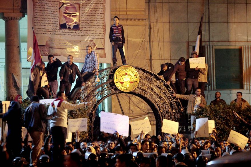 Egyptian anti-government activists chant slogans as they gather inside the Lawyers Syndicate in downtown Cairo on Wednesday. Beefed-up police forces on the streets quickly moved in and used tear gas and beatings to disperse demonstrations. (Associated Press)