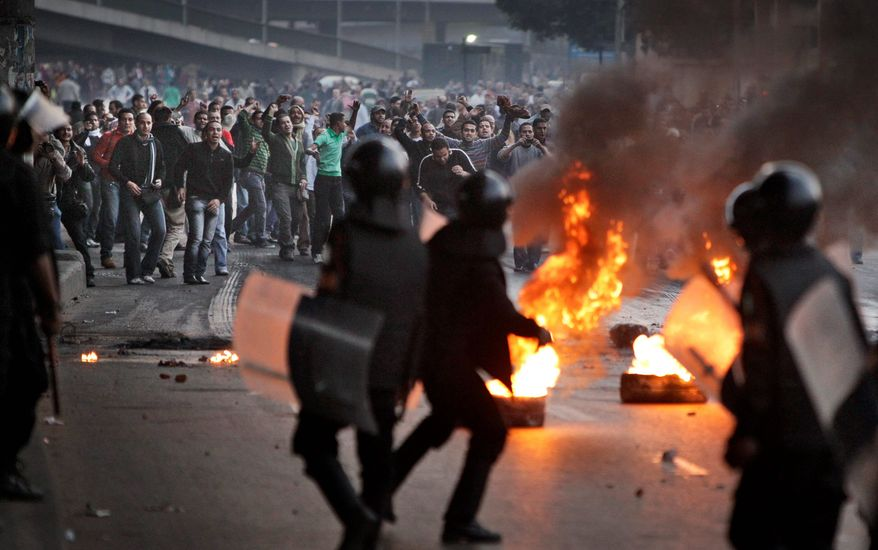 Egyptian riot police clash with anti-government activists in Cairo on Wednesday. The activists clashed with police for a second day Wednesday in defiance of an official ban on any protests. (Associated Press)