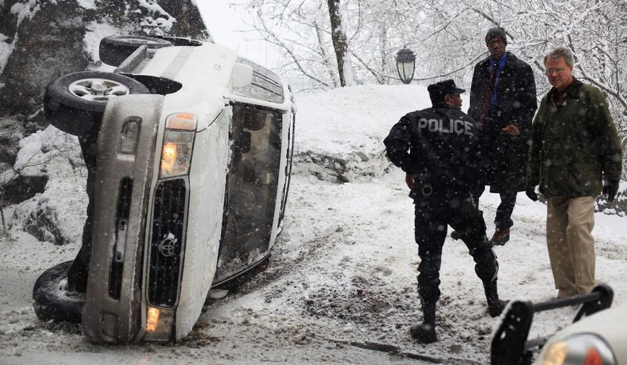 A vehicle lies on the side of the road along Kelly Drive during a winter storm in Philadelphia on Wednesday. The Philadelphia area could get 4 to 8 inches, and high winds are expected before the storm moves out early Thursday. (Associated Press)