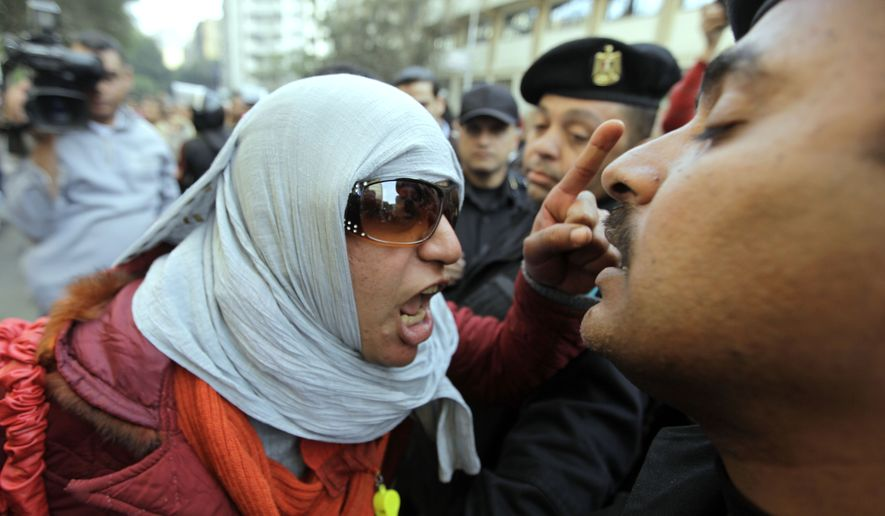 An angry Egyptian activist shouts at anti-riot policemen who block the way leading to journalists syndicate in downtown Cairo on Wednesday. A small gathering of Egyptian anti-government activists tried to stage a second day of protests in Cairo Wednesday in defiance of a ban on any gatherings, but police quickly moved in and used force to disperse the group. (Associated Press)