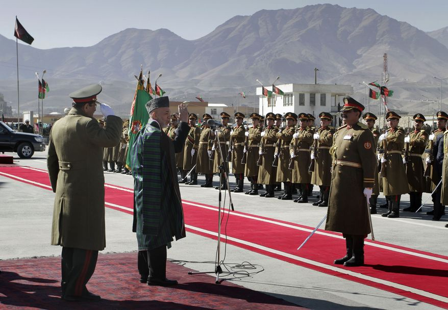 Afghan President Hamid Karzai salutes to members of a guard of honor during the inauguration of new parliament in Kabul, Afghanistan on Wednesday, Jan.26, 2011. (AP Photo/Musadeq Sadeq)