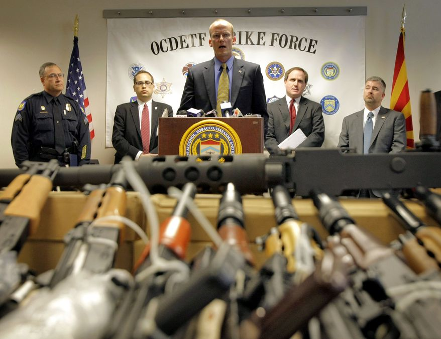 Bill Newell, special agent in charge of the ATF Phoenix, speaks Tuesday behind a cache of seized weapons in Phoenix. A grand jury indicted more than 30 persons on firearms charges for participating in a ring that bought hundreds of guns that were to be smuggled into Mexico for use by a drug cartel. (Associated Press)