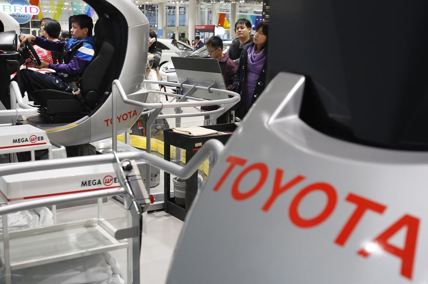 Visitors enjoy at the showroom of Toyota Motor Corp. in Tokyo Wednesday, Jan. 26, 2011. Toyota is recalling nearly 1.7 million vehicles worldwide for various defects that may cause fuel leakage and other problems, the latest in quality control woes for the Japanese automaker. (AP Photo/Shizuo Kambayashi)