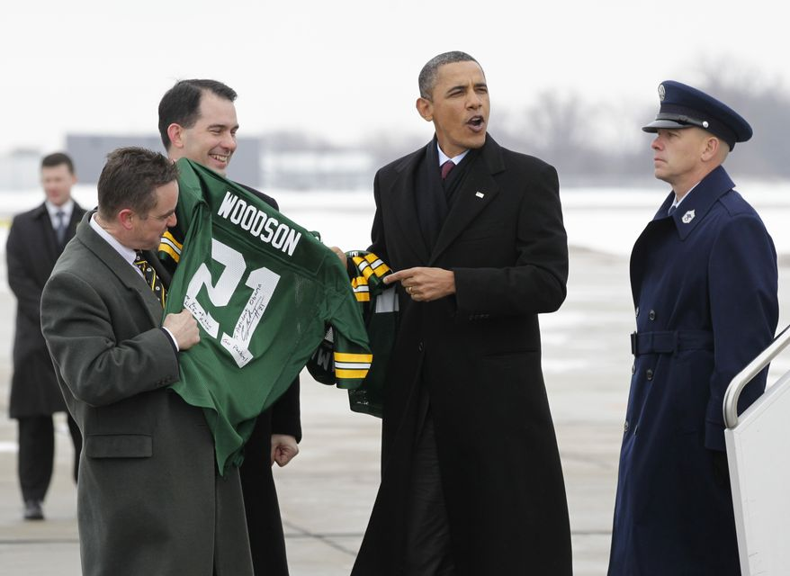 President Barack Obama receives an autographed Green Bay Packers Charles Woodson from Wisconsin Gov. Scott Walker, center, and Green Bay Mayor Jim Schmitt, upon his arrival in Green Bay, Wis., Wednesday, Jan. 26, 2011, en route to nearby Manitowoc, Wis., where he will a tour renewable-energy factories and talk about jobs and the economy. Obama, a Chicago native, predicted the Chicago Bears would beat Green Bay in the NFC Championship game. (AP Photo/J. Scott Applewhite)