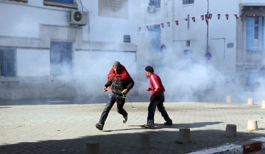 Protesters run away from tear gas during clashes in Tunis, Wednesday Jan. 26, 2011. The clashes broke out in front of the prime minister's office as the caretaker government prepared to announce adjustments to its lineup. Hundreds of protesters in the capital are pressuring the interim government to get rid of allies of ousted President Zine El Abidine Ben Ali. (AP Photo/Rafael Yaghobzadeh)