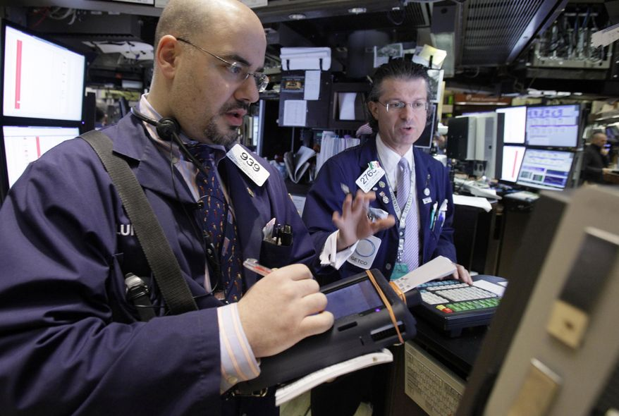 In this Jan. 25, 2011 photo, trader Luigi Muccitelli, left, and specialist Donald Civitanova work on the floor of the New York Stock Exchange. (AP Photo/Richard Drew)