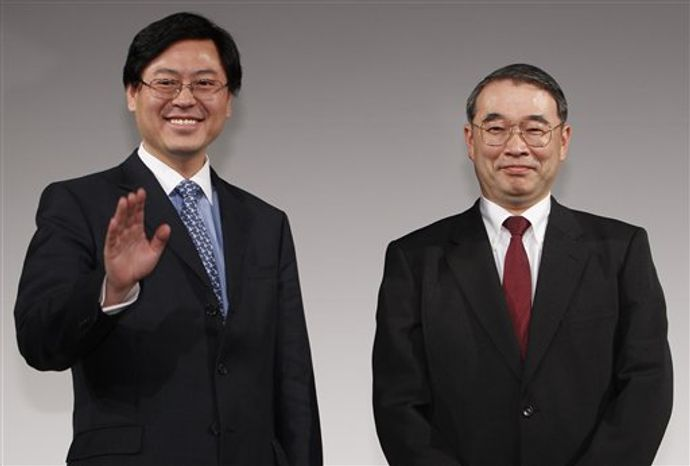 Lenovo Group Chief Executive Officer Yang Yuanqing, left, shakes hands with NEC President Nobuhiro Endo during a joint press conference in Tokyo Thursday, Jan. 27, 2011. NEC and China's Lenovo said Thursday they will join forces to create the largest personal computer business in Japan. (AP Photo/Shizuo Kambayashi)