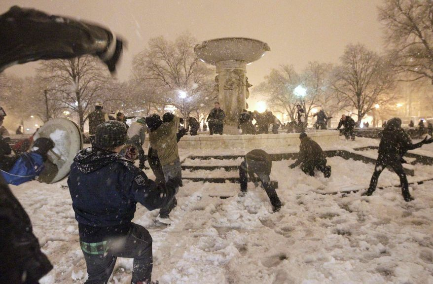 A snowball fight breaks out at Dupont Circle in Washington in the still-falling snow on Wednesday, Jan. 26, 2011. (AP Photo/Pablo Monsivais)