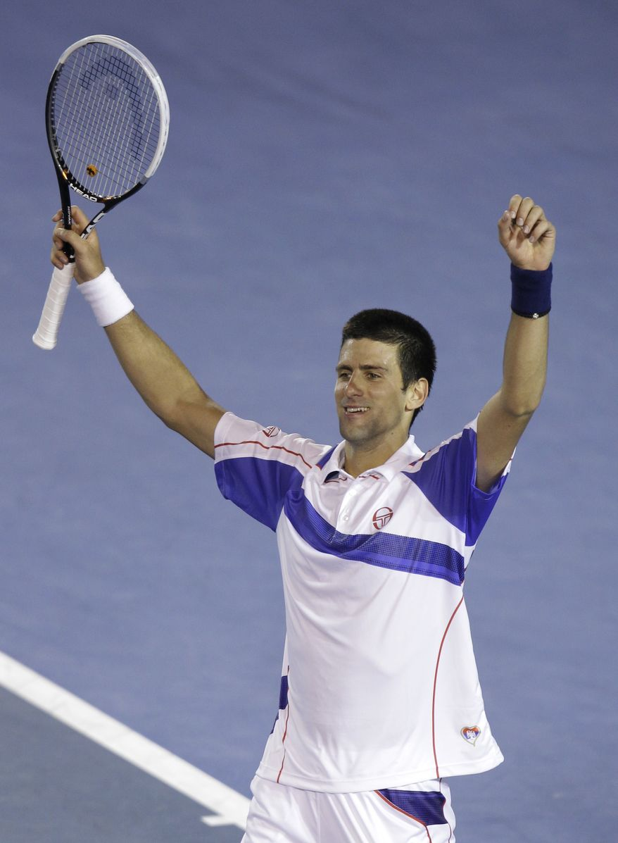 Serbia's Novak Djokovic raises his arms as he celebrates his win over Switzerland's Roger Federer in their semifinal at the Australian Open tennis championships in Melbourne, Australia, on Thursday, Jan. 27, 2011. (AP Photo/Mark Baker)
