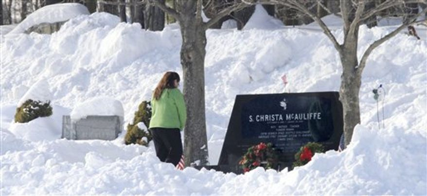 Former Concord High School student Kelly Garfield, who had Christa McAuliffe as a homeroom teacher, stands Friday, Jan. 28, 2011, in Concord, N.H., at her gravesite at 11:38, 25-years after the shuttle Challenger exploded, killing McAuliffe and the rest of the crew. (AP Photo/Jim Cole)