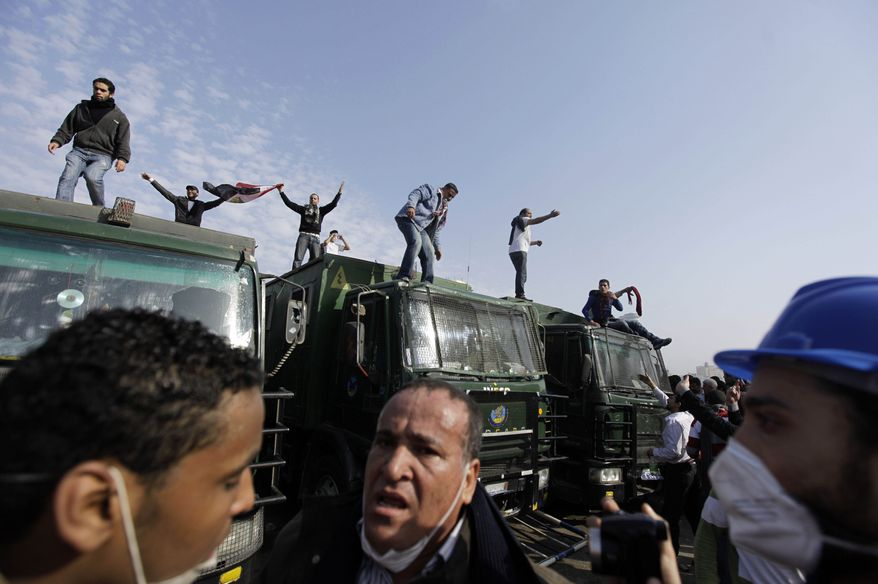 Egyptian anti-government activists are seen atop police trucks during clashes with police in Cairo Friday, Jan. 28, 2011. Tens of thousands of anti-government protesters poured into the streets of Egypt Friday, stoning and confronting police who fired back with rubber bullets and tear gas in the most violent and chaotic scenes yet in the challenge to President Hosni Mubarak's 30-year rule. (AP Photo/Ben Curtis)