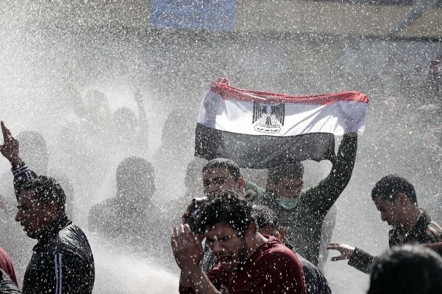 An Egyptian protester flashes Egypt's flag as anti-riot policemen use water canon against protesters in Cairo Friday, Jan. 28, 2011. Egyptian activists protested for a fourth day as social networking sites called for a mass rally in the capital Cairo after Friday prayers, keeping up the momentum of the country's largest anti-government protests in years. (AP Photo/ Lefteris Pitarakis)