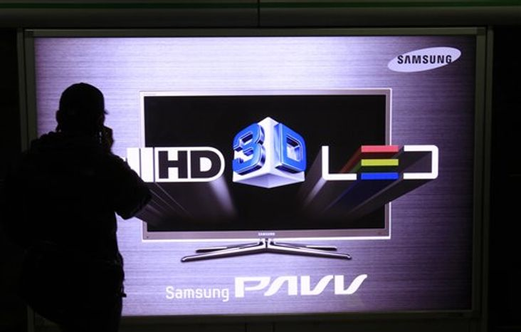 A man uses his mobile phone near the sign advertising Samsung Electronics Co's HD TV screen at a subway station in Seoul, South Korea, Friday, Jan. 28, 2011. Samsung Electronics said net profit rose 13 percent in the fourth quarter of 2010 amid higher sales of semiconductors and smartphones as the technology giant rounded out a record year for profits and revenue.  (AP Photo/ Lee Jin-man)