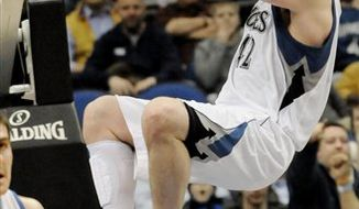 Minnesota Timberwolves' Kevin Love hangs onto the rim after a dunk in the second half of an NBA basketball game against the Oklahoma City Thunder Wednesday, Jan. 26, 2011 in Minneapolis. The Thunder won 118-117 in overtime. Love led the Timberwolves with 31 points and 21 rebounds. (AP Photo/Jim Mone)