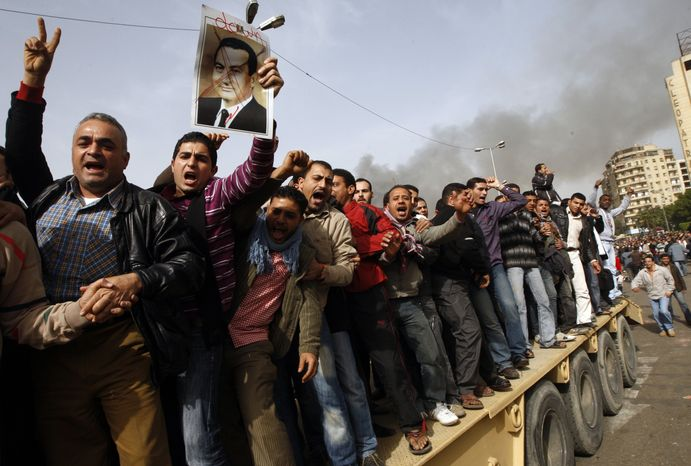 Egyptian anti-government activists, one of them holding a crossed-out portrait of Egyptian President Hosni Mubarak, chant slogans as they protest in downtown Cairo, Egypt, on Saturday, Jan. 29, 2011. (AP Photo/Khalil Hamra)