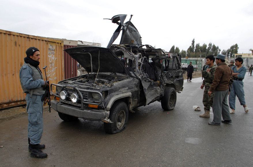 An Afghan policeman stands near a vehicle which carried the deputy governor of Kandahar province, Abdul Latif Ashna, in Kandahar, south of Kabul, Afghanistan, on Saturday, Jan. 29, 2011. A suicide bomber riding a motorcycle packed with explosives rammed into the car, killing the deputy governor and wounding three of his bodyguards, the Interior Ministry said. (AP Photo/Allauddin Khan)