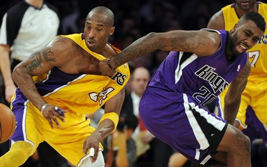 Los Angeles Lakers shooting guard Kobe Bryant, left, steals the ball as Sacramento Kings small forward Donte Greene pulls his jersey during the first half of their NBA basketball game, Friday, Jan. 28, 2011, in Los Angeles.   (AP Photo/Mark J. Terrill)