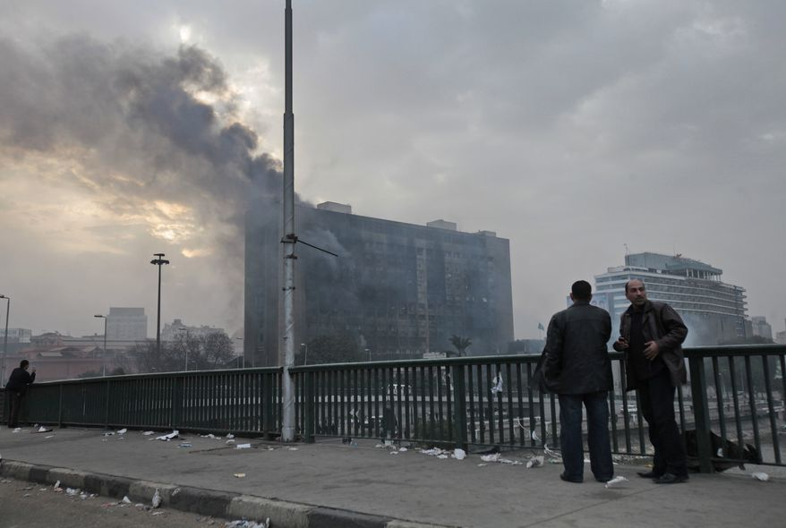 Smoke billows from a building following overnight clashes between Egyptian security forces and anti-government activists in Cairo, Egypt, Saturday, Jan. 29, 2011. (AP Photo/Lefteris Pitarakis)