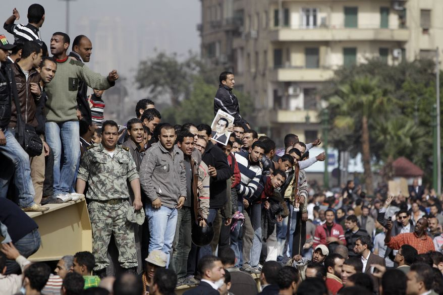 Egyptian anti-government protesters climb atop an Egyptian army armored personnel carrier in Cairo, Egypt, on Saturday, Jan. 29, 2011. (AP Photo/Ben Curtis)