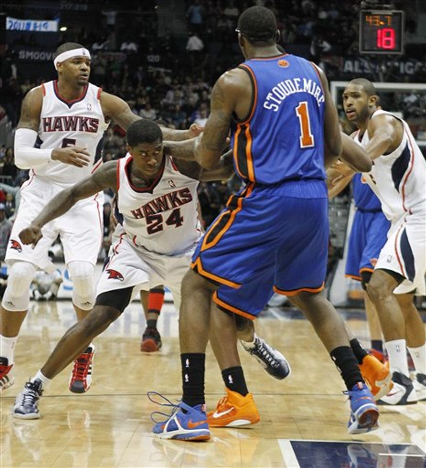 An official (52) tries to break up a fight between Atlanta Hawks' Marvin Williams, left, and New York forward Shawne Williams (3) in the fourth quarter of an NBA basketball game Friday, Jan. 28, 2011, in Atlanta. (AP Photo/John Bazemore)