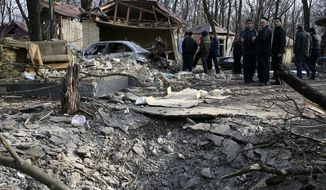 ** FILE ** Investigators work at the site of an explosion near a cafe in the town of Khasavyurt, Dagestan, southern Russia, on Saturday, Jan. 15, 2011. An explosive-laden car exploded near the White Nights cafe in the town of Khasavyurt in Dagestan, killing and wounding several persons. The town borders Chechnya, where two conflicts with the federal government in Moscow fueled the rise of Islamic militancy in the Northern Caucasus region. (AP Photo/Ruslan Alibekov, NewsTeam)