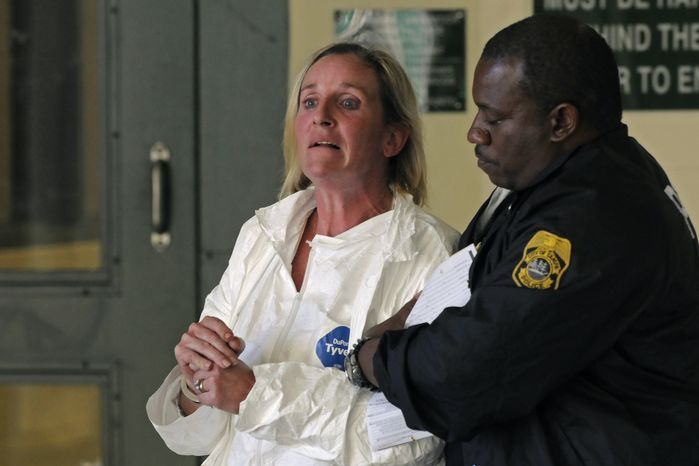 Tampa Police officer escorts Julie Powers Schenecker to Orient Road Jail on Friday, Jan. 28, 2011, in Tampa, Fla. Police said she admitted the slayings after officers found her covered in blood on the back porch of her home Friday morning, police spokeswoman Laura McElroy said. (AP Photo/St. Petersburg Times, Bryan Thomas)