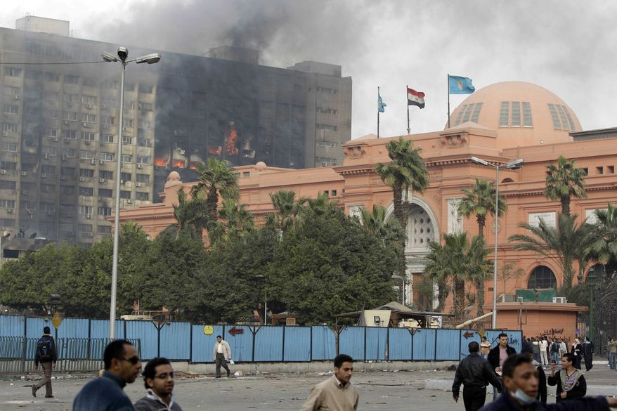 The Egyptian museum is seen intact, right, as smoke billows from the ruling National Democratic party building, torched by anti government protesters overnight, in central Cairo, Egypt, on Saturday, Jan. 29, 2011. (AP Photo/Ben Curtis)