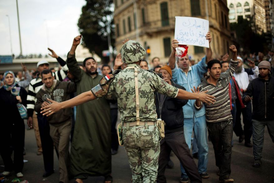 DEFIANT: Protesters march past an Egyptian soldier Sunday in Cairo as they move toward Tahrir Square during a sixth day of demonstrations against the government. (Associated Press)