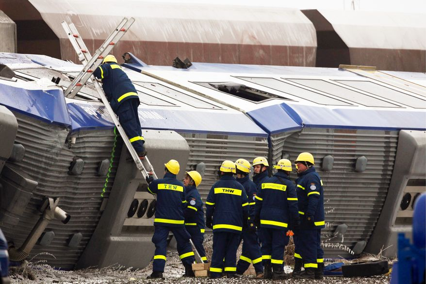 Police inspect the overturned engine of a passenger train after a train crash in Hordorf, eastern Germany, on Sunday. (Associated Press)