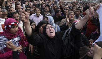Women react during a demonstration in Cairo on Sunday, Jan. 30, 2011, as the Arab world's most populous nation appeared to be swiftly moving closer to a point at which it either dissolves into widespread chaos or the military expands its presence and control of the streets. (AP Photo/Ahmed Ali)