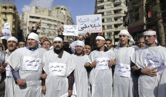 Egyptians dressed in white shrouds to show their readiness to die for their cause, demonstrate in Cairo on Monday Jan. 31, 2011. A coalition of opposition groups called for a million people to take to Cairo's streets Tuesday to ratchet up pressure for President Hosni Mubarak to leave. Posters on the shroudS reads: 'This my shroud for the sake of Egypt'. (AP Photo/Ben Curtis)